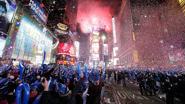 Revellers cheer as confetti falls during New Year celebrations in Times Square in New York January 1, 2011. REUTERS/Lucas Jackson (UNITED STATES - Tags: ANNIVERSARY SOCIETY IMAGES OF THE DAY)